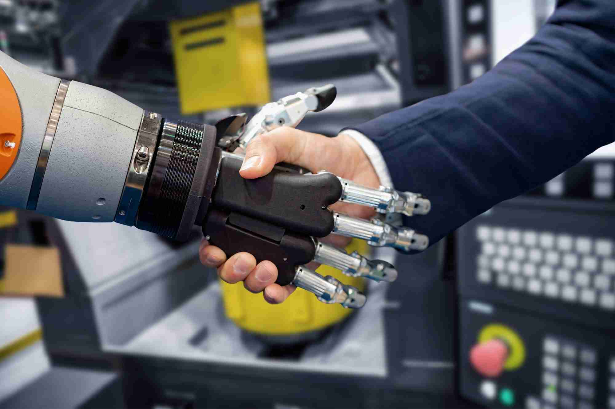 Hand of a businessman shaking hands with a Android robot.
